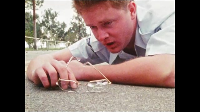 1980s: Man at bus stop drops grenade. Man yells grenade, soldiers runs, grenade explodes, man rolls away. Man lays on street, looks up, holds broken glasses. Man exits house, checks door lock.