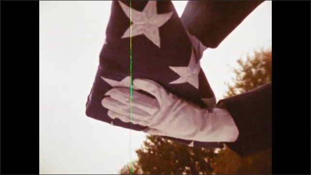 1980s: Soldiers pass folded up flag. Soldier holds flag.