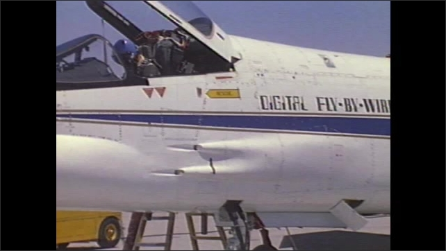 1990s: Pilot climbs into cockpit of jet. F-8 jet taxis on runway. Men close hatch on bottom of jet. Control panel and instruments of plane. Pilot affixes breathing mask in cockpit.