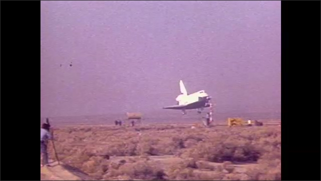 1990s: Men use camera on tripod to record aircraft shuttle landing.