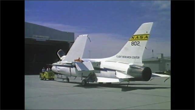 """1990s: F-8 Crusader flies in the air, text """"Digital Fly-By-Wire"""" on the aircraft. Aircraft with text """"NASA 802"""" is driven by a small vehicle. Aircraft lands."""