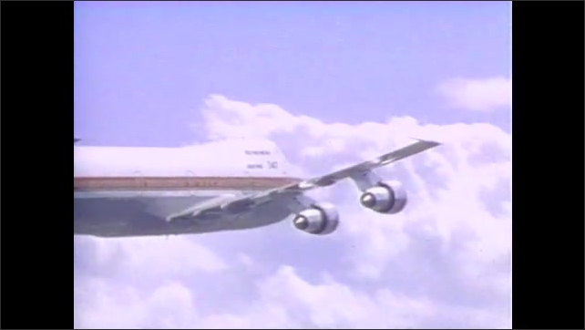 1990s: Pilot in the airplane cockpit in the air. Airplane flies, sky with clouds.