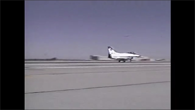 1990s: Hand moves joystick. Man operates flight simulator. Two men stand next to aircraft. Aircraft departs. Aircraft flies against sky with clouds. Aircraft in the air.