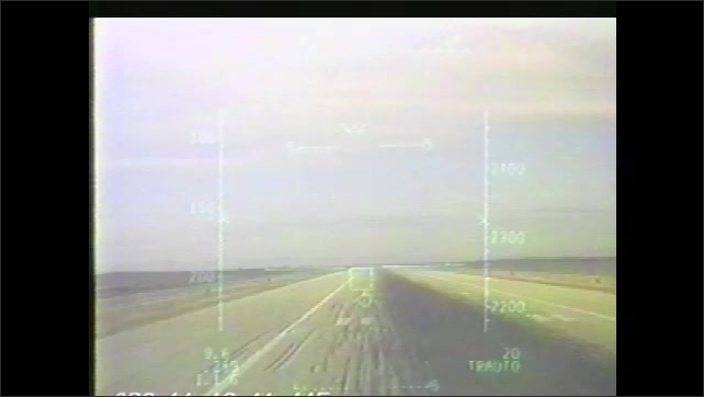 1990s: F-15 aircraft departs. Flight path stabilizer over landing strip. Two aircrafts fly against blue sky.