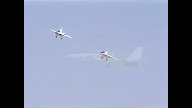 1990s: Two aircrafts fly against blue sky. F-15 flies against blue sky. Airplane lands.