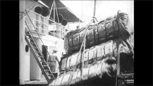 1940s: crane lifting cargo onto large ship as men help guide them down safely