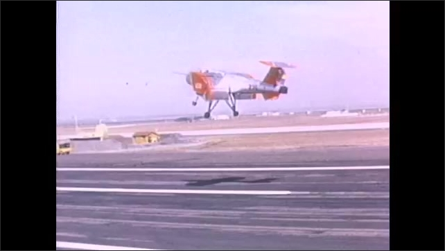 1960s: Army plane travels in hovering path over runway. Aircraft hovers over aerial landscape.