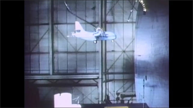 1960s: Man in facility turns model aircraft toward him. Model plane hovers in wind tunnel simulation. Aircraft in sky spins, nose downward.