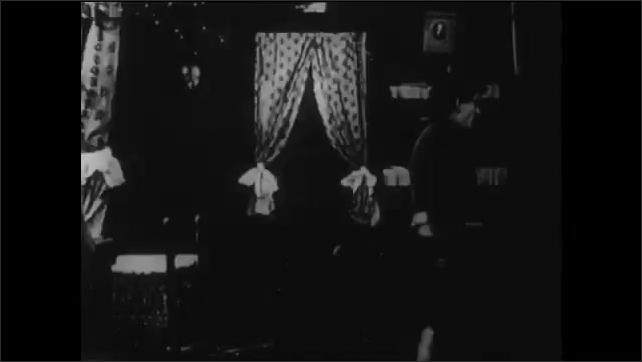 1910s: man in uniform kneels on floor and begs as woman hits and drags him near door. soldier hides in bedroom and climbs out window as woman pleads. man lands outside house as battle rages nearby.