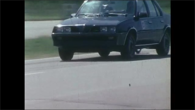 1980s: UNITED STATES: vehicles drive along test track. Vehicle with wheel at back. Car screeches to halt.