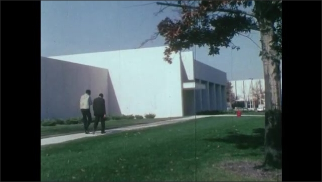1980s: UNITED STATES: car drives down test hill. Men walk outside technical centre. Engineer at work. Wind tunnel test of car