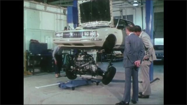 1980s: UNITED STATES: spring by wheel on car. General Motors cradle design. Engine of car