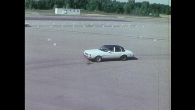 1980s: UNITED STATES: car on proving ground track. Driver tests brakes on car. Man drives front wheel drive car along track