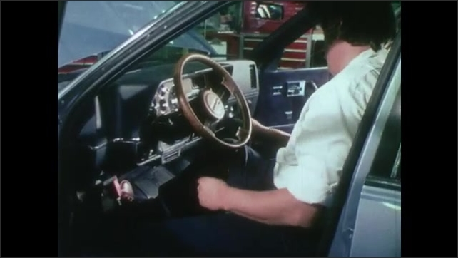 1980s: UNITED STATES: white car on proving ground track. Monitoring on dash board of test car. On board computer in car. Man sets dial in car. Prototype car on track