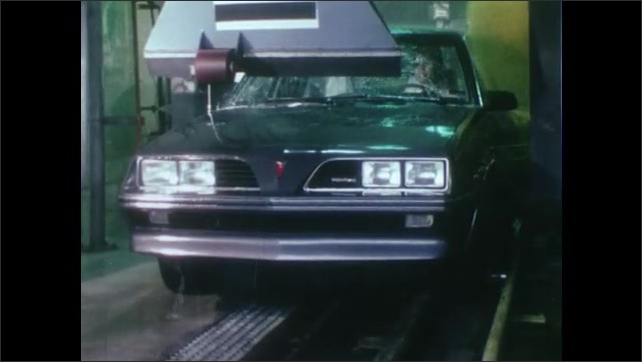 1980s: UNITED STATES: man hoists car on lift. Car in automatic wash. Man attaches chains to car during testing