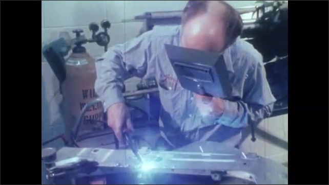1980s: UNITED STATES: man welds metal in lab. Man tights vice. Fuel economy research at proving ground