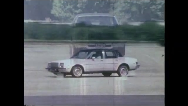 1980s: UNITED STATES: car drives along wet surface. Car skids on wet surface. Car drives around cones.
