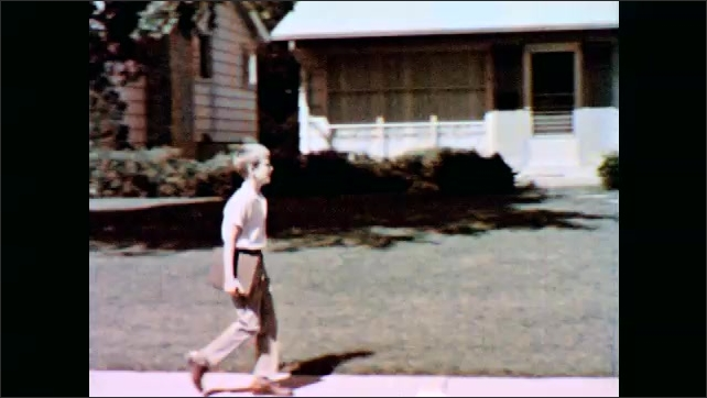 1960s: UNITED STATES: man drives to work in car. Boy walks to school. Family in suburbs. By walks past tall buildings