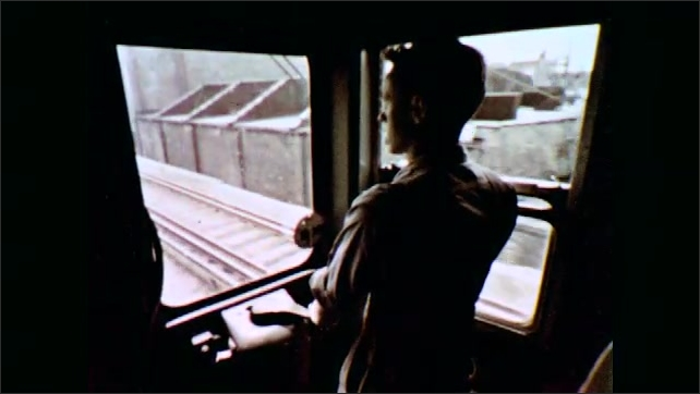 1960s: UNITED STATES: view along railway tracks. Boys hold hands. Boys walk to school. Train passes buildings. Man drives train. Train in subway.