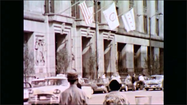 1960s: UNITED STATES: close up of head lamp. Cars in street. Cars in large car park. Police officer directs traffic. Columns on building. People in conference