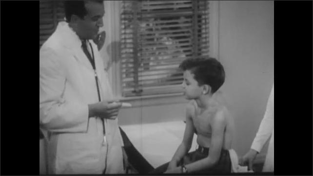 1940s: Doctor checks boy's throat with tongue depressor. Doctor talks to boy on examination table. Nurse helps boy put on shirt.