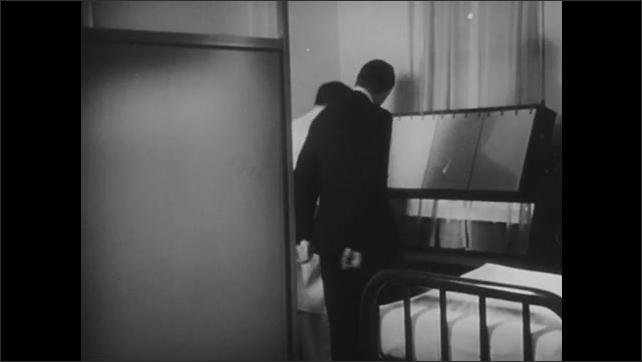 1940s: Doctors examine girl's broken arm. Doctors examine x-rays of broken arm on light box.