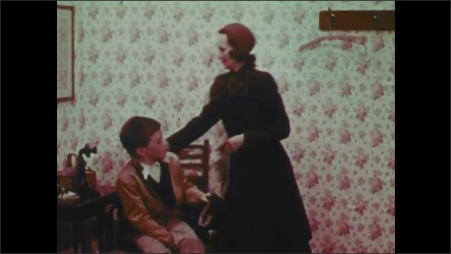 1960s: Boy sits in chair, talks to woman standing nearby. Woman buttons coat and her and boy walk away. Car drives down road. Woman exits building.