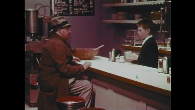 1960s: Man sits at counter, talks. Boy pours coffee, puts coffee on counter.