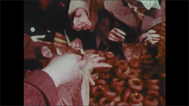 1960s: Boys gather around donut machine. Man brings tray of milk to boys. Child tries to get through crowd. People buy and eat donuts. Boy grabs handfuls of donuts.