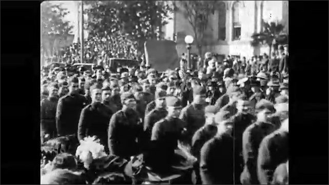1920s: People celebrating in large parade. Brass band marches down street in parade followed by soldiers. Crowd watches soldiers march. Nurses wave to soldiers.