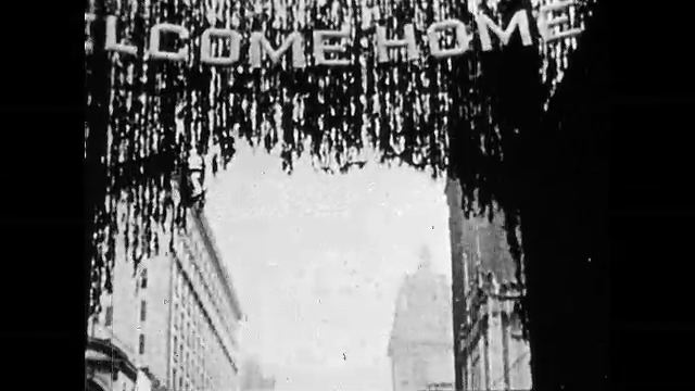 1920s: Under a Welcome Home sign, a large crowd marches down street. Large group marches down street. Soldiers marching. Large crowd celebrating. Soldier surrounded by people, hugs woman.