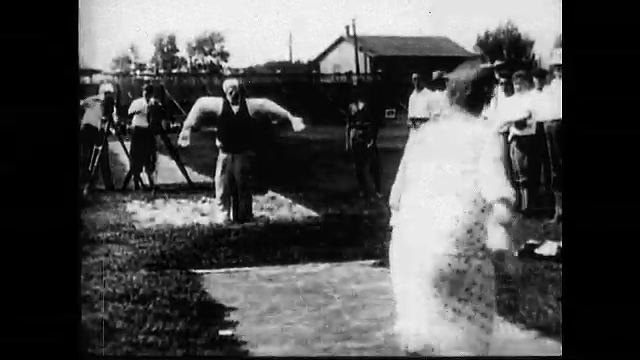 1920s: Woman throws objects at target dummy. Dummy is struck by objects. Women walk in formation in uniforms. Woman sit at tables with sewing machines. Women marching in uniform.