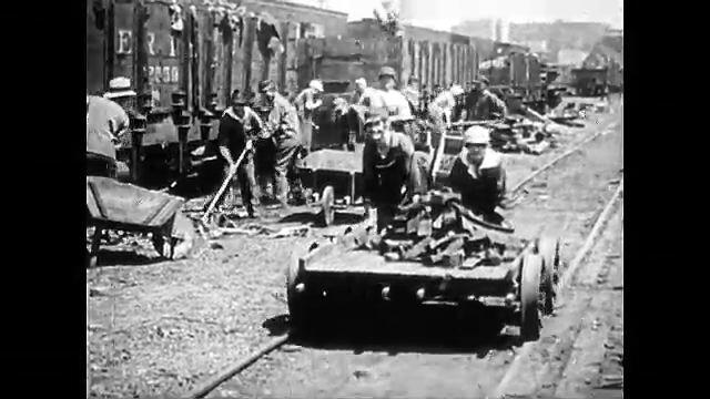 1920s: Women working on railroad loading train car, push cart on tracks. Woman conducts traffic. Women in uniforms in line. Woman pulls self up smokestack on board. Women dance on top of smokestack.