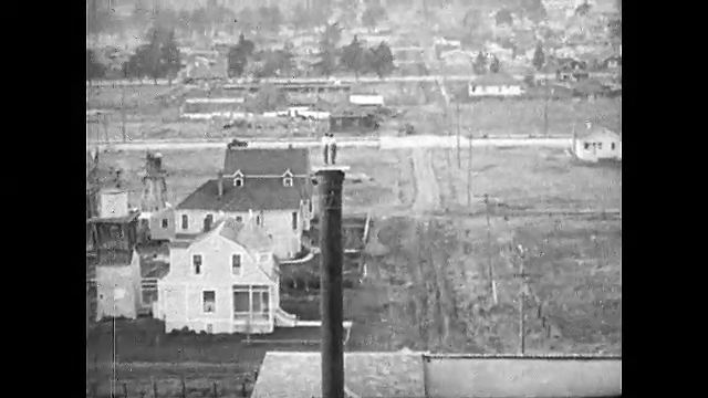 1920s: Two women dance on top of smokestack. Man guides train into stop. Woman exits train engine. Women work cleaning train. Women chopping down trees. Women saw tree down. Woman stacking lumber.