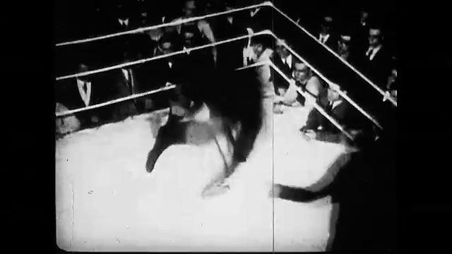 1920s: Women stack lumber. Woman wrestles man in ring. Women knocks gun away from man. Woman knocks man down, twice. Woman boxes man. Women run race. Women sit on fence singing. Woman paints mural.
