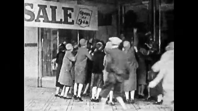 1920s: Group of people clamor outside department store for sale. Man inside store signals doors to open. Doors open, people run in store. People grab clothes in store. Women modeling clothes.