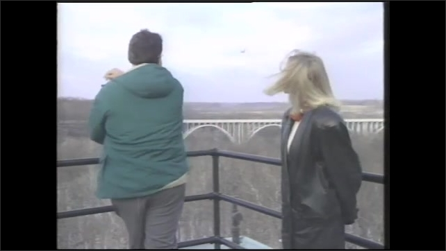 1990s: Man holding snowball talks to woman standing on deck above forest. Man throws snowball off deck. Woman and man continue talking.