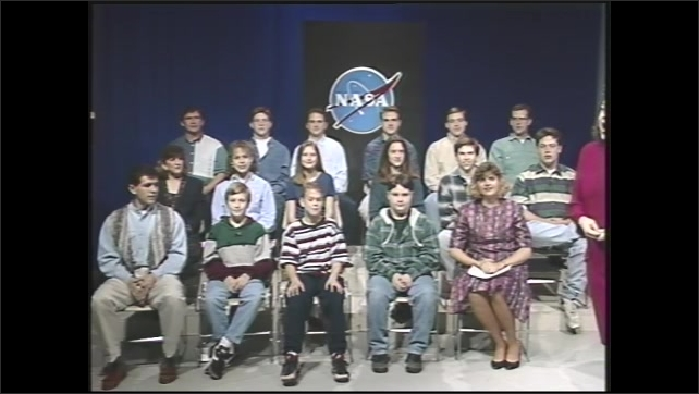 1990s: People are various ages sit in folding chairs in three rows in front of NASA backdrop. Woman talks.