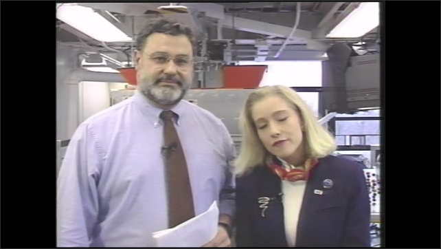 1990s: Digital display of numbers on machine conducting experiment. Man and woman talking in front of science equipment.