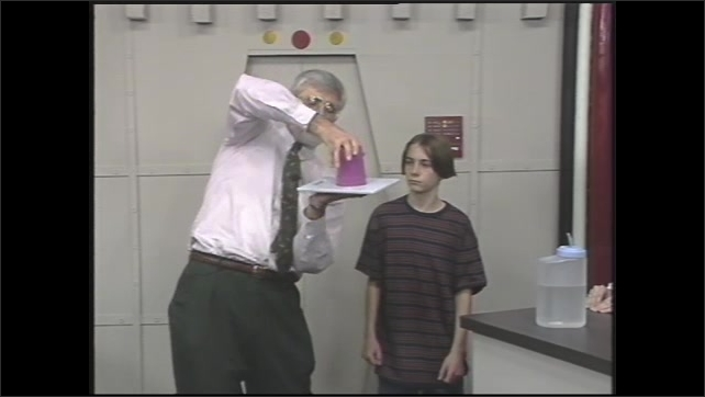 1990s: Man stands next to boy, talking, while filling cup with water from jug. Man places board over cup of water, and flips cup and board over, handing it to boy.
