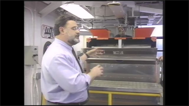 1990s: Man and woman stand in front of science equipment as man talks, pointing at equipment.