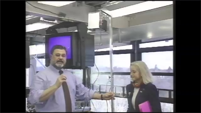 1990s: Man talks while holding and placing transparent container inside box that woman next to him is holding. Man pulls string attached to box and pulley, raising box up.