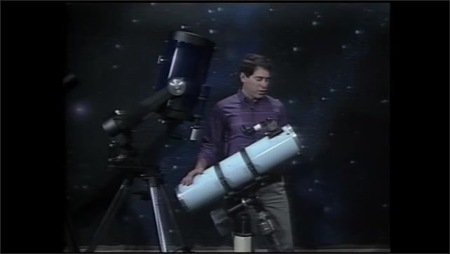 1990s: Man stands talking next to two large telescopes on tripods. Man swings one of the telescopes around on tripod head.