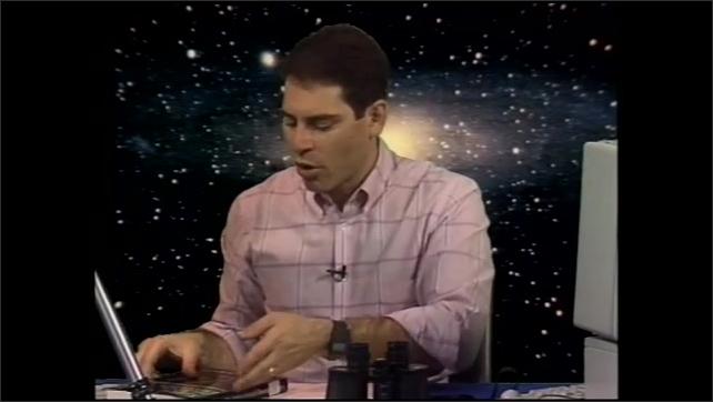 1990s: Man seated in front of background of stars talks while holding up books on astronomy and binocular usage.