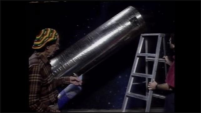 1990s: Two men stand in front of large telescopes talking. Man wheels in smaller telescope as they have conversation.