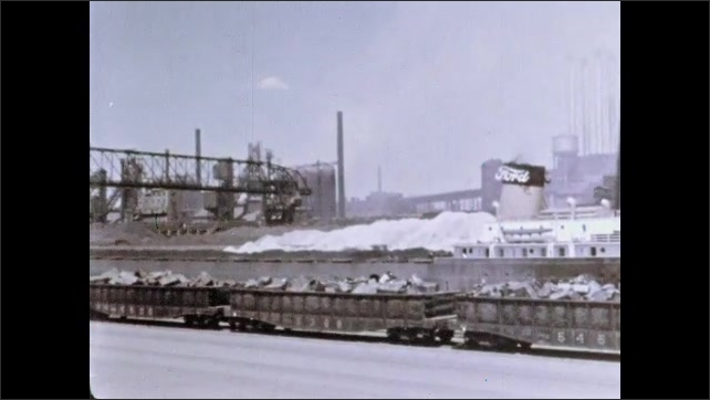 1960s: Tugboat in harbor, cranes over ship. Port, train cars piled high. Industrial area by river, smoke stacks billow, factories, silo.