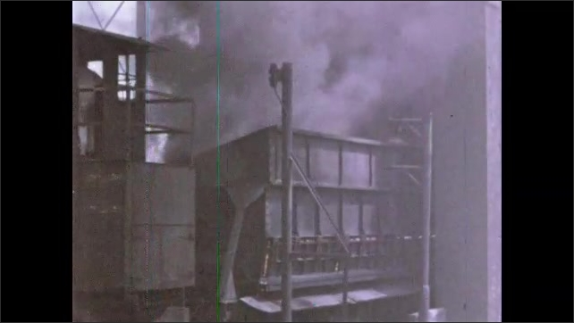 1960s: Industrial area, thick black smoke billows from dumpster, dumpster travels down track. People walk outside factory, steam rises, car.