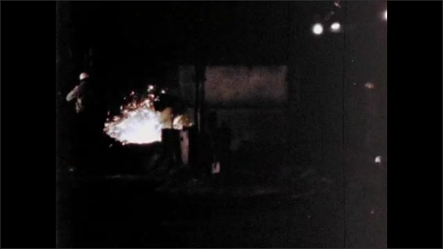 1960s: Industrial area, night time, group of men in hard hats use shovels. Molten metal flares up, waves of sparks rise up.