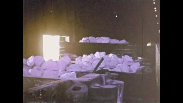1960s: Industrial area, heavy equipment pushes large batch of scrap metal out of warehouse. Warehouse door rises, equipment pushes hopper of rocks out, arm retracts.