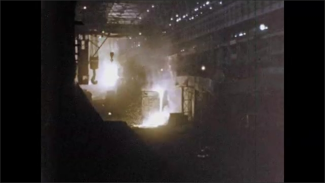 1960s: Industrial area, man in hard hat oversees operation of heavy equipment, sparks fly, molten metal pours, glows.